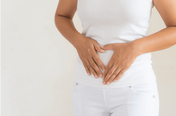 Woman with uterine fibroids holding pregnant stomach